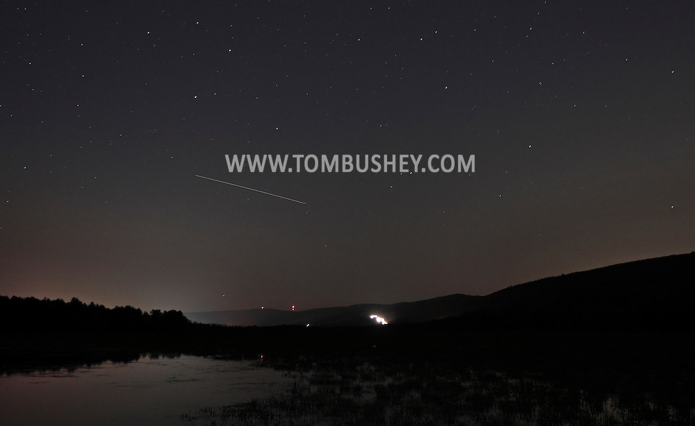 Mamakating, New York - The International Space Station appears as a streak across the sky during a 30-second exposure at the Bashakill Wildlife Management Area on the night of April 19, 2012. The white streaks in the background are from cars driving west on Route 17.
