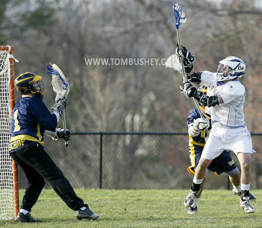 Warwick's Tyler Young, right, leaps to take a shot on Pine Bush goalie Joey Schof during a game in Warwick on Friday, April 15, 2011.