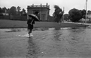 "Flooding at the Dodder..1986..26.08.1986..08.26.1986..28th August 1986..As a result of Hurricane Charly (Charlie) heavy overnight rainfall was the cause of severe flooding in the Donnybrook/Ballsbridge areas of Dublin. In a period of just 12 hours it was stated that 8 inches of rain had fallen. The Dodder,long regarded as a ""Flashy"" river, burst its banks and caused great hardship to families in the 300 or so homes which were flooded. Council workers and the Fire Brigades did their best to try and alleviate some of the problems by removing debris and pumping out some of the homes affected..Note: ""Flashy"" is a term given to a river which is prone to flooding as a result of heavy or sustained rainfall...Image of a pedestrian braving the elements as he crosses a flooded street. Gum boots or wellingtons were essential."