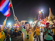 "05 MAY 2104 - BANGKOK, THAILAND:  A man carrying a Thai flag shouts ""Long Live the King"" during candlelight vigil for Bhumibol Adulyadej, the King of Thailand, on Ratchadamnoen Ave in front of Sanam Luang in Bangkok. Thousands of Thais packed the area around Sanam Luang and the Grand Palace Monday evening for a special ceremony to mark Coronation Day, which honored the 64th anniversary of the coronation of Bhumibol Adulyadej, the King of Thailand. Many of the people also support the anti-government movement led by Suthep Thaugsuban. Most of the anti-government protesters are conservative supporters of the monarchy.   PHOTO BY JACK KURTZ"