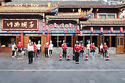 Uniformed Restaurant staff wait outside for customers. Chengdu, Kuan Zhai Xiang Zi historic city, Sichuan, China