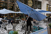 Bar customers straighten large umbrellas just blown over during a sudden but brief gust of wind in Leicester Square, on 19th October 2017, in London, England.