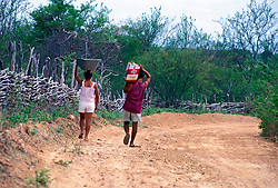 Pernambuco, Brasil..Pessoas transportando agua em estrada de terra no sertao./ People carrying water in soil road in the desert..Foto © Luiz Prado/Argosfoto