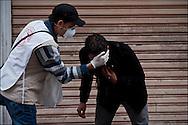 Un bénévole du croissant-rouge Tunisien vient en aide aux manifestants en leur nettoyant le visage avec du lait afin de calmer les brûlures liées aux gaz lacrymogènes utilisés par les forces de police. //  Des affrontements entre la police et les manifestants ont éclaté dans le centre de Tunis, notamment avenue Habib Bourguiba, faisant (selon Associated Press) 3 morts (prétendument par balle) et 12 blessés parmi les manifestants, Tunis le 26 février 2011.