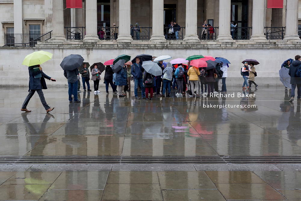 During seasonal rain, reflections of visitors and their umbrellas on the pavement of Trafalgar Square, on 9th May 2019, in London, England.