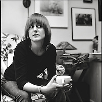 A woman sitting holding a cup