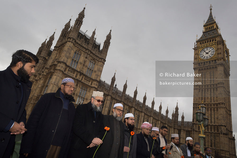 Londoners and police gather on Westminster Bridge, the scene of the Terrorist attack 7 days ago in which 4 people died and others severely injured, on 29th March 2017, London, England. Hundreds crossed the Thames in a silent vigil to commemorate those who died at 2.40pm when Khalid Masood drove into crowds on the bridge before stabbing a police officer at the nearby Palace of Westminster. The crowds fell silent, many bowing their heads, among them were dozens of young Muslim children and members of the Ahmadiyya community.