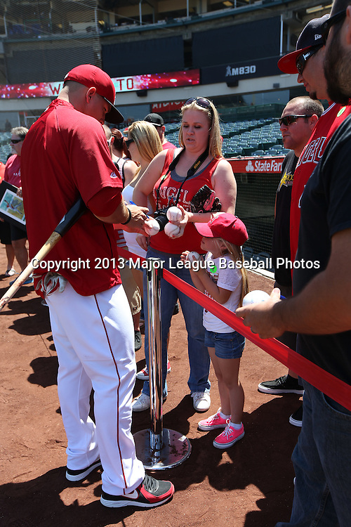 ANAHEIM, CA - JUNE 15:  Mike Trout #27 of the Los Angeles Angels of Anaheim autographs a baseball after batting practice before the game against the New York Yankees on Saturday, June 15, 2013 at Angel Stadium in Anaheim, California. The Angels won the game 6-2. (Photo by Paul Spinelli/MLB Photos via Getty Images) *** Local Caption *** Mike Trout