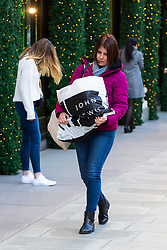 A woman uses both arms to carry a heavy bag of shopping on Oxford Street in London as high street retailers are facing their quietest Christmas UK high streets face quietest Christmas since credit crunch. London, December 13 2018.