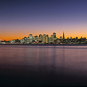 San Franciso California and Oakland Bay Bridge at sunset, view across San Francisco Bay from Treasure Island