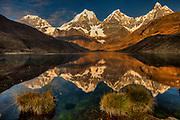 Carhuacocha lake, sunrise reflections on Siula Grande, Yerupaja and Jirishanca peaks, Andes mountains, Cordillera Huayhuash, northern Peru