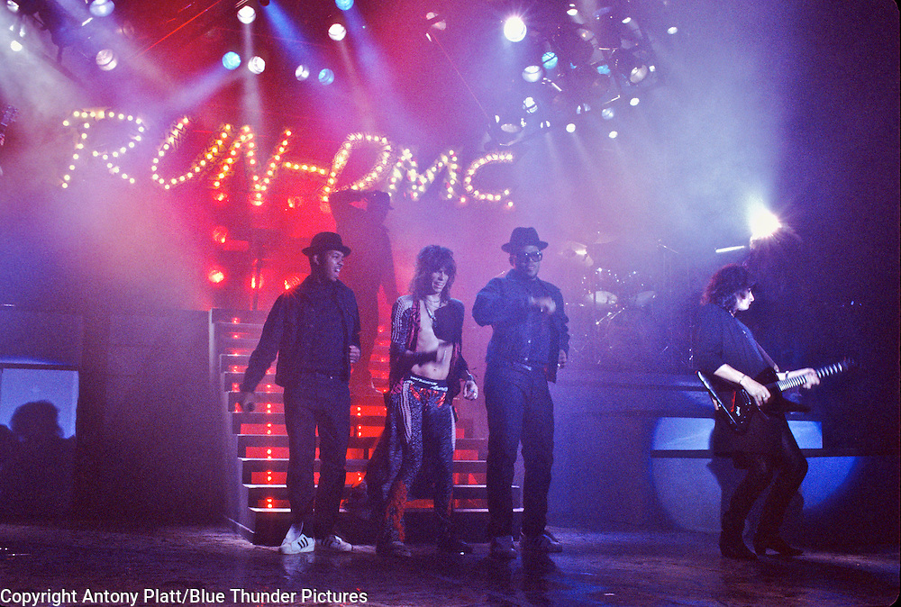Jam Master Jay, Run, Steve Tyler, DMC & Joe Perry on stage in New York City in 1986 during the Classic 80's Rock & Roll meets Rap Event. The Music Video for the Aerosmith, RUN-DMC collaboration Walk this Way!