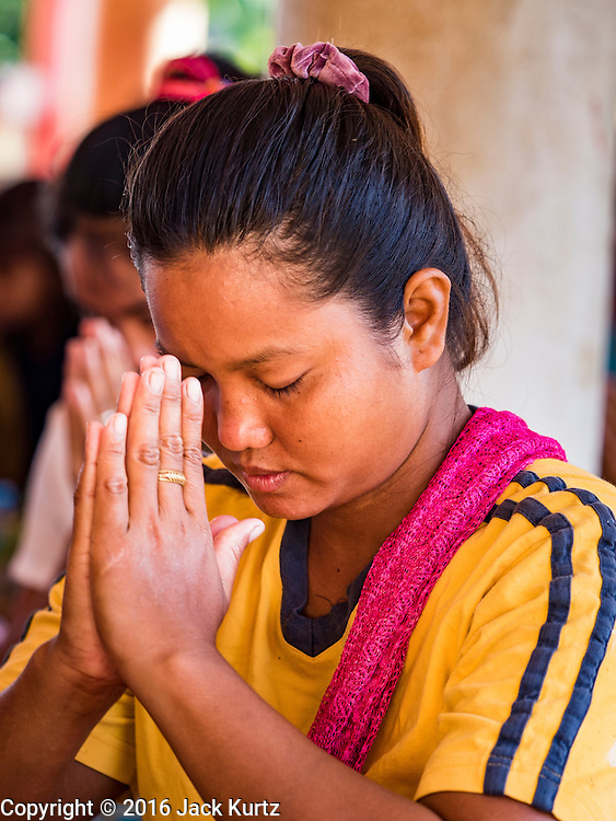 19 JUNE 2016 - DON KHONE, CHAMPASAK, LAOS: A woman prays in a Buddhist temple in Don Khone village on Don Khone Island. Don Khone Island, one of the larger islands in the 4,000 Islands chain on the Mekong River in southern Laos. The island has become a backpacker hot spot, there are lots of guest houses and small restaurants on the north end of the island.    PHOTO BY JACK KURTZ