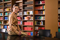 Young woman sitting on desk in library portrait