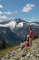 Adult male hiker with red jacket and  backpack relaxing on Ragged Ridge. Mount Logan is in the distance. North Cascades National Park Washington