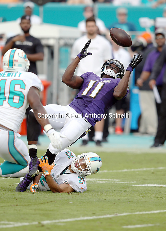 Baltimore Ravens wide receiver Kamar Aiken (11) is covered by Miami Dolphins cornerback Brent Grimes (21) as he catches an 11 yard first quarter pass good for a first down while falling backwards during the 2015 week 13 regular season NFL football game against the Miami Dolphins on Sunday, Dec. 6, 2015 in Miami Gardens, Fla. The Dolphins won the game 15-13. (©Paul Anthony Spinelli)