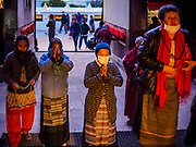 17 MARCH 2017 - KATHMANDU, NEPAL: People pray as they enter a monastery near Boudhanath Stupa in Kathmandu. The stupa is the holiest site in Nepali Buddhism. It is also the center of the Tibetan exile community in Kathmandu. The Stupa was badly damaged in the 2015 earthquake but was one of the first buildings renovated.     PHOTO BY JACK KURTZ