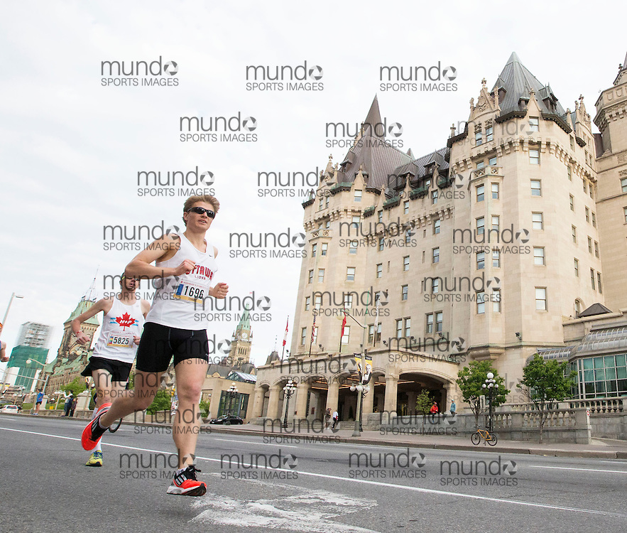 (Ottawa, Canada---24 May 2015) Tommy Des Brisay (1696) runs past the Chateau Laurier at the start of the marathon during the Tamarack Run Ottawa Race Weekend.