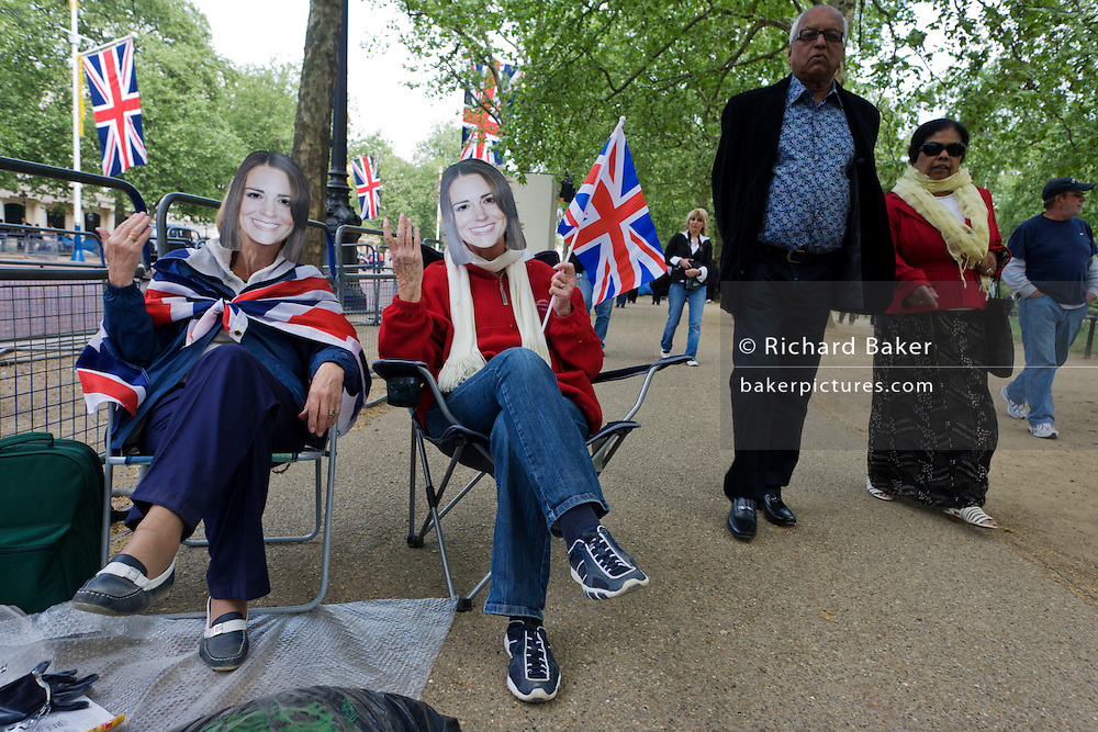 24 hours before the royal marriage of Prince William and Kate Middleton, two women royalists wearing Kate Middleton masks that are widely available sit in camping chairs and offering their adoring public royal waves. Taking place on Friday 30th April in front of millions of Britons and foreign tourists (many American), the crowds are already gathering to claim their ideal locations in the front rows along the procession route.