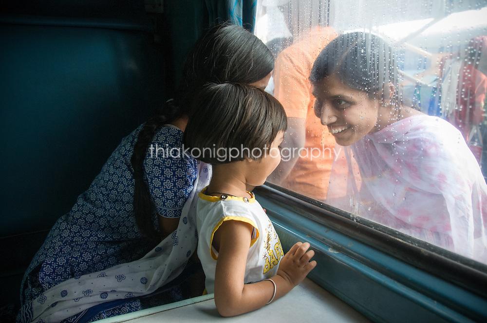 Women smiling at girl through train window, India.