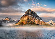 The mountains peaks of Grinnel Point, Mount Wilbur and Mount Gould are a cold backdrop to the icy glacial water of Swiftcurrent Lake on a frozen morning. The Hotel situated on this lake at Many Glacier is a popular tourist destination. It was originally an exclusive resort built by the Great Northern Railway and finished in 1915. Glacier National Park, Montana, USA