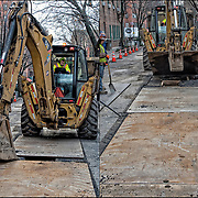 Saveway Construction Enterprises backhoe operator lifting steel covering so crew can  dig up street for replacement of new gas pipes in Waverly Place,  Greenwich Village, NYC. <br />