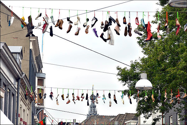 Nederland, the netherlands,  Nijmegen, 20-7-2015Een winkelier van schoenen heeft boven de ziekerstraat enkele touwen met schoenen gehangen. Symbool voor de vierdaagse. Op de achtergrond de stevenstoren. The International Four Day Marches Nijmegen, or Vierdaagse, is the largest marching event in the world. It is organized every year in Nijmegen mid-July as a means of promoting sport and exercise. Participants walk 30, 40 or 50 kilometers daily, and on completion, receive a royally approved medal, Vierdaagsekruisje. The participants are mostly civilians, but there are also a few thousand military participants. The maximum number of 45,000 registrations has been reached. More than a hundred countries have been represented in the Marches over the years. FOTO: FLIP FRANSSEN/ HOLLANDSE HOOGTE