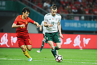 Gareth Bale, right, of Wales national football team kicks the ball to make a pass against Wang Shenchao of Chinese national men's football team in the semi-final match during the 2018 Gree China Cup International Football Championship in Nanning city, south China's Guangxi Zhuang Autonomous Region, 22 March 2018.