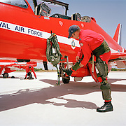 Flight Lieutenant Dan Simmons of the elite 'Red Arrows', Britain's prestigious Royal Air Force aerobatic team, zips up his g-pants before climbing into his Hawk jet. G-pants counteract the effects of high gravity stresses that jet-fighters impose on the human body, automatically inflating and squeezing blood back to the thorax and head when blood drains towards the legs. As he attaches the zipper, he rests his straight right leg on a retractable step which helps him and his ground crew engineers to gain access to the cockpit, high above the ground. Hanging from another part of his airplane is his life-vest which he will wear around his neck, whilst in flight. Flight Lieutenant Simmons wears heavy-duty black boots which are regulation footwear for flying personnel and dressed in his red flying suit that is famous around the world.