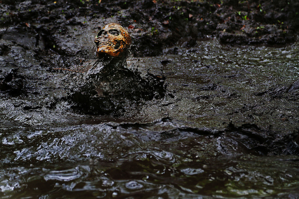Wearing a skull mask, Derrick Moreau emerges from muddy water during the The Ultimate Challenge Mud Run in Gaston, SC, Saturday, April 11, 2015. Established in 1993, the Mud Run has grown to attract enlistee's from across the United States, Canada and around the world.