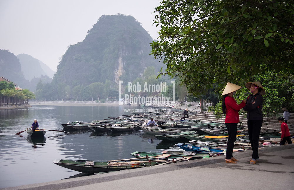 Two women wearing conical hats chatting on the quayside at Tam Coc. Approximately 1300 people work at this location, and share the job of rowing  visitors along the 5km boat ride up the river surrounded by spectacular limestone karst scenery.