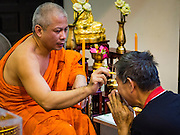 21 NOVEMBER 2015 - BANGKOK, THAILAND: A monk annoints people at the Wat Saket temple fair. Wat Saket is on a man-made hill in the historic section of Bangkok. The temple has golden spire that is 260 feet high which was the highest point in Bangkok for more than 100 years. The temple construction began in the 1800s in the reign of King Rama III and was completed in the reign of King Rama IV. The annual temple fair is held on the 12th lunar month, for nine days around the November full moon. During the fair a red cloth (reminiscent of a monk's robe) is placed around the Golden Mount while the temple grounds hosts Thai traditional theatre, food stalls and traditional shows.     PHOTO BY JACK KURTZ