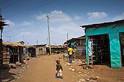 A young boy walks across the street in the Kiandutu slum, Thika, Kenya.