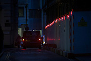 A delivery courier's van's red brake lights and construction hoarding lighting in the City of London.
