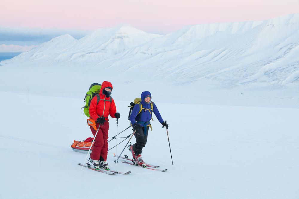 Michelle Blade (left) and Mylène Jacquemart ski across Breinosa, Svalbard, above Adventadlen, at dawn.