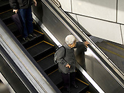 elderly woman standing on an escalator Japan