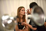 Model Mathilde Brandi has lipstick applied backstage before the DKNY collection is modeled during Fashion Week, Wednesday, Sept. 16, 2015, in New York.  (AP Photo/Diane Bondareff)