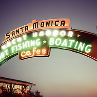 "Santa Monica Pier sign retro photo. The fampous Santa Monica Pier sign says ""Santa Monica Yacht Harbor Sport Fishing Boating Cafes"". Santa Monica Pier is a landmark located in Los Angeles County Southern California and has an amusement park with a ferris wheel, roller coaster, restaurants, and other attractions. Photo has vintage 1960's tone."