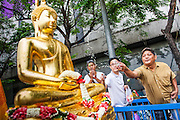 12 APRIL 2013 - BANGKOK, THAILAND:   Thais sprinkle scented oils on the Phra Buddha Sihing while it is paraded through the streets of Bangkok on the first day of Songrkran. The Phra Buddha Sihing, a revered statue of the Buddha, is carried by truck through the streets of Bangkok so people can make offerings and bathe it in scented oils. Songkran is celebrated in Thailand as the traditional New Year's Day from 13 to 16 April. The date of the festival was originally set by astrological calculation, but it is now fixed. If the days fall on a weekend, the missed days are taken on the weekdays immediately following. Songkran is in the hottest time of the year in Thailand, at the end of the dry season and provides an excuse for people to cool off in friendly water fights that take place throughout the country. The traditional Thai New Year has been a national holiday since 1940, when Thailand moved the first day of the year to January 1. The first day of the holiday period is generally the most devout and many people go to temples to make merit and offer prayers for the new year.<br />   PHOTO BY JACK KURTZ
