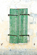Traditional weather worn faded wooden shutters on house in Ile de Re, France