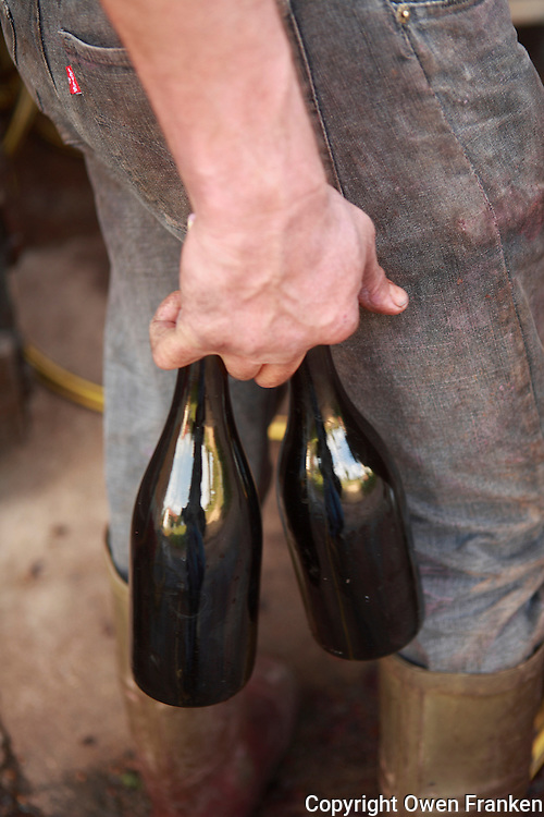 winemakers' hands and two bottles