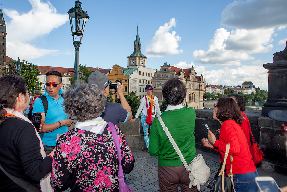 A group of Asian tourist is photographing each other one by one on the same spot at Charles Bridge. The Charles Bridge (Czech: Karlův most) is a famous historic bridge that crosses the Vltava river in Prague, Czech Republic and is probably the Nr.1 tourists magnet in the city.