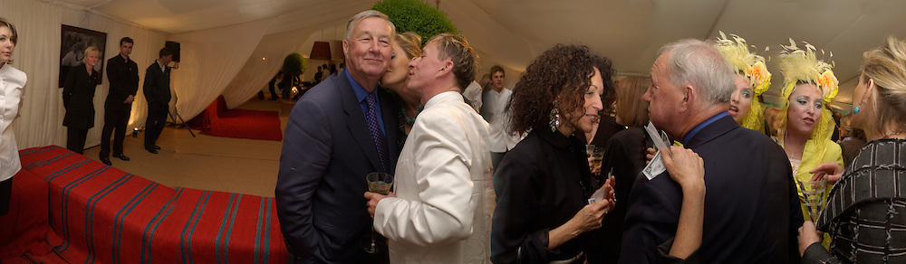 Sir Terence Conran being kissed by his wife ( Lady ? Victoria ), and son from a previous wife, Jasper Conran, Tricia Guild ( ?) Katrine Moynihan  ( Boorman) in yellowLaunch of Jasper Conran Man and Jasper Conran Woman  perfumes,  Chelsea Physic Garden. 1 May 2003. © Copyright Photograph by Dafydd Jones 66 Stockwell Park Rd. London SW9 0DA Tel 020 7733 0108 www.dafjones.com