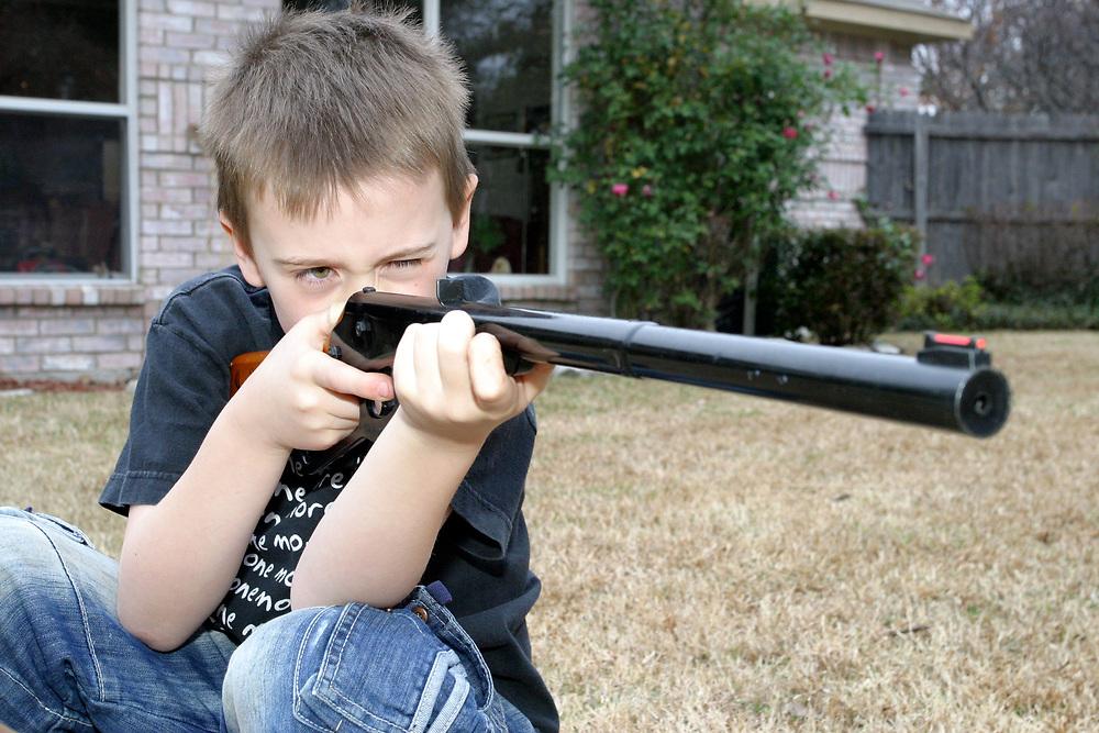 Young boy shooting a BB gun, Dallas, Texas, USA
