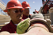 PINEDALE, WY - Halliburton cement crew workers Marcus Villefanco, of Pecos, TX, and William Stevens, of Brownsville, TX,  prepare their gear at Caza Drill Rig 86, under contract by Questar, on the Pinedale Anticline on August 20, 2005. As part of well completion, the crew will pressurize their lines to 9000 lbs and inject cement to the bottom of the 14,000 foot well where it will squeeze around the base of the drill hole casing and come back up the outside, isolating the different strata. When the cement sets another team will come in to hydraulically fracture the strata to stimulate gas production, a new technique which has made this gas field a profitable endeavor. While many residents are thankful for the work created by the gas field, there are concerns of environmental damage, air quality issues, and marring of the view shed many newer residents moved to the area for. Pinedale currently has the lowest unemployment rate in the state and is experiencing another boom cycle both in real estate and in energy as natural gas production in two nearby gas fields ramps up for year-round production.