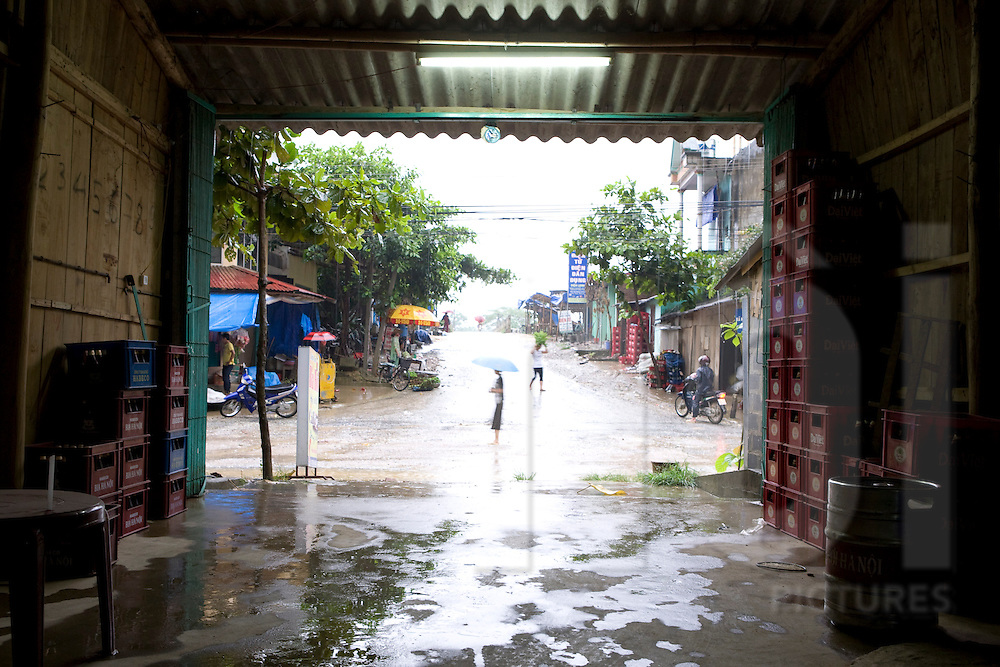 Street by a rainy day viewed from an alcohol retailer's warehouse. Vietnam, Asia.