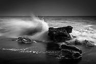 A sea wave splashing into the rocks on the beach