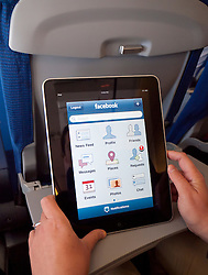 Woman using iPad computer tablet to check Facebook internet website on passenger aircraft
