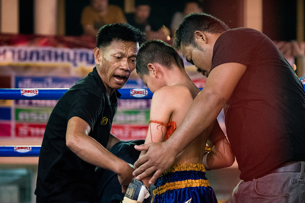 A young Muay Thai fighter gets instructions between rounds during a boxing match at a festival in Nakhon Nayok Thailand.