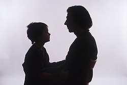 Silhouette of father and son sitting together,